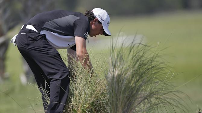 Rory McIlroy of Northern Ireland looks for his ball in the weeds on the third hole during the third round of the PGA Championship golf tournament on the Ocean Course of the Kiawah Island Golf Resort in Kiawah Island, S.C., Saturday, Aug. 11, 2012. (AP Photo/Evan Vucci)