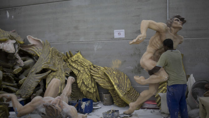In this photo taken Tuesday, Jan. 22, 2013, a man caries a Carnival float sculpture at the Grande Rio Samba school in Rio de Janeiro, Brazil. Yet it's from warehouses like this one that Rio's over-the-top glitz-and-glam Carnival parades emerge, as they will Monday night for the final round of a two-day performance. The internationally renowned competition between 12 elite samba groups dazzles more than a billion spectators in person and on TV for two days, but it takes nearly a year and hundreds of workers, many of them volunteers, to pull each one together. (AP Photo/Felipe Dana)