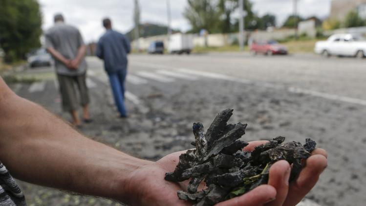 A man shows pieces of shrapnel collected after what locals say, was recent shelling by Ukrainian forces in Donetsk