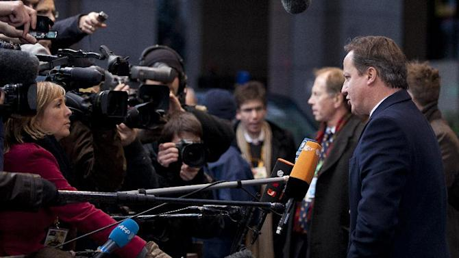 British Prime Minister David Cameron, right, speaks with the media as he arrives for an EU summit in Brussels on Thursday, Dec. 13, 2012. In one whirlwind morning, the European Union nations agreed on the foundation of a fully-fledged banking union and Greece's euro partners approved billions of euros in bailout loans that will prevent the nation from going bankrupt. (AP Photo/Virginia Mayo)
