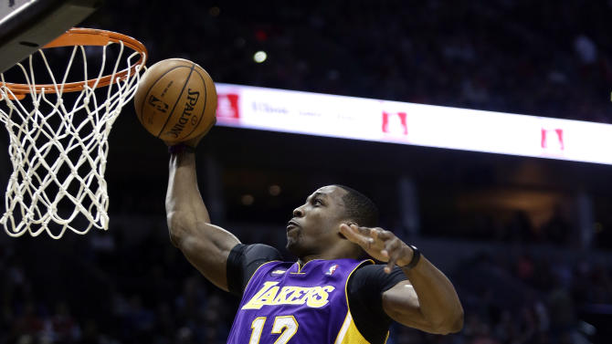 Los Angeles Lakers center Dwight Howard, left, drives to the basket past Portland Trail Blazers forward LaMarcus Aldridge during the first quarter of an NBA basketball game in Portland, Ore., Wednesday, April 10, 2013. (AP Photo/Don Ryan)