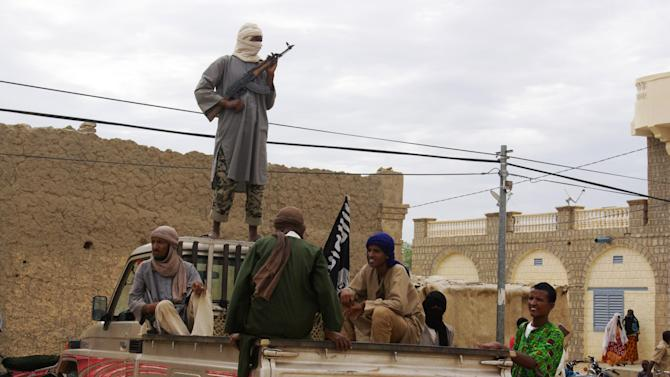 FILE - In this Aug. 31, 2012 file photo, fighters from the al-Qaida-linked Islamist group Ansar Dine stand guard in Timbuktu, Mali, as they prepare to publicly lash a member of the Islamic Police found guilty of adultery. Mali once enjoyed a reputation as one of West Africa's most stable democracies with more than 90 percent of its 15 million people practicing a moderate form of Islam. That changed in April 2012, when Islamist extremists took over the main cities in the country's north amid disarray following a military coup and began enforcing strict Shariah law. (AP Photo/File)