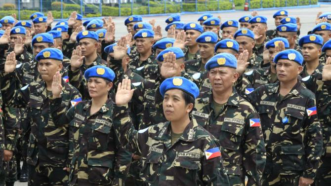 Members of the Philippines contingent joining the United Nations Peacekeeping Force in Haiti take an oath during a sending-off ceremony at the Villamor air base in Pasay city