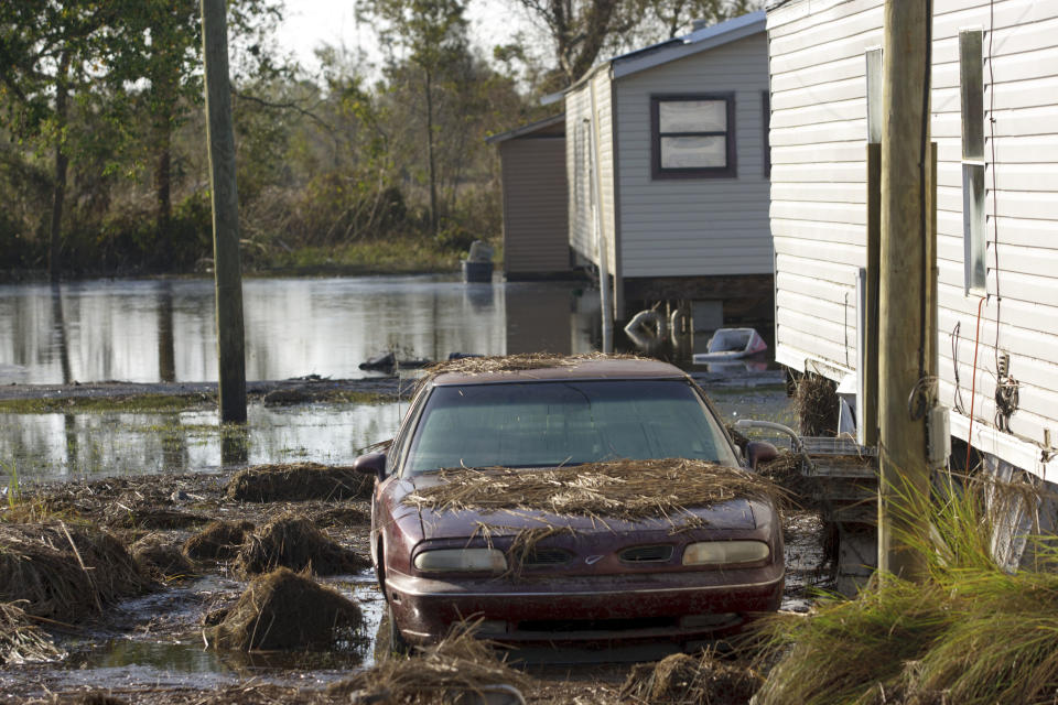 A car is covered in debris while other homes are surrounded by floodwaters in Ironton, La. after Hurricane Isaac near Louisiana Hwy 23 in Plaquemines Parish Monday, Sept. 3, 2012. (AP Photo/Matthew Hinton)