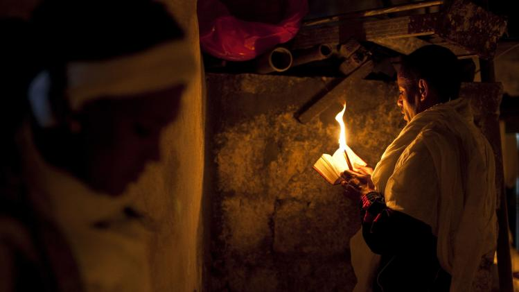 An Ethiopian Orthodox worshipper holds candles during the Holy Fire ceremony at the Ethiopian section of the Church of the Holy Sepulchre in Jerusalem's Old City
