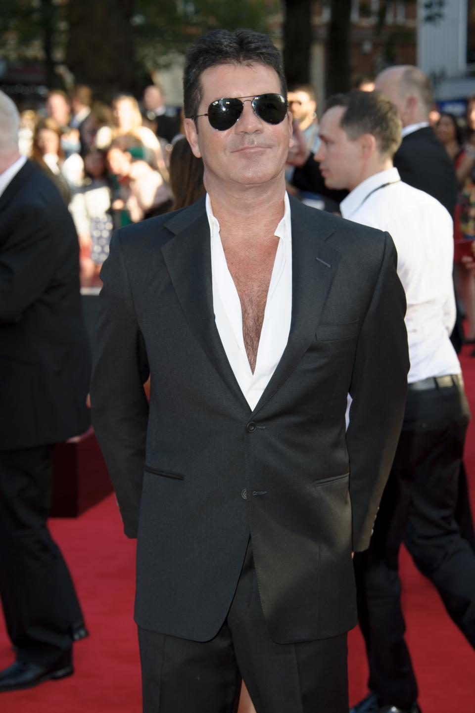 British producer Simon Cowell arrives for the UK Premiere of 'One Direction: This Is Us 3D' at a central London cinema, Tuesday, Aug. 20, 2013. (Photo by Jonathan Short/Invision/AP)