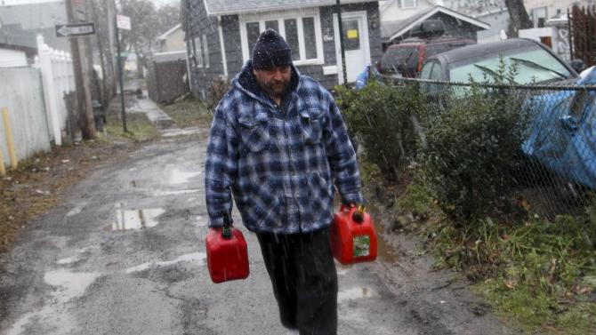 Joe Graham delivers some gas in the snow to a neighbor for use in her generator in the New Dorp section of Staten Island, N.Y. Wednesday, Nov. 7, 2012.  A nor'easter blustered into New York and New Jersey on Wednesday, threatening to swamp homes all over again, plunge neighborhoods back into darkness and inflict more misery on tens of thousands of people still reeling from Superstorm Sandy.  (AP Photo/Seth Wenig)