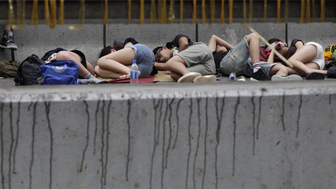 Pro-democracy student protesters sleep on an occupied main street outside of the government complex in Hong Kong, Thursday, Oct. 2, 2014. Raising the stakes in their standoff with the authorities, Hong Kong's pro-democracy protesters threatened to occupy key government buildings unless the territory's top official resigns by the end of the day Thursday. (AP Photo/Wally Santana)