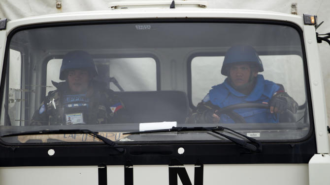A U.N. peacekeeper from the Philippines drives a UNDOF vehicle as it leaves the  Ziouani camp to cross into Syria at the Quneitra Crossing between Syria and the Israeli-controlled Golan Heights, Friday, March 8, 2013. The Philippine government said Syrian rebels failed to release 21 Filipino U.N. peacekeepers Friday and stuck to their demands for repositioning of Syrian government forces before any handover. The 21 peacekeepers were seized Wednesday near the Syrian village of Jamlah, just a kilometer (less than a mile) from the Israeli-controlled Golan Heights, where the U.N. force has patrolled a cease-fire line between Israel and Syria for nearly four decades. (AP Photo/Ariel Schalit)