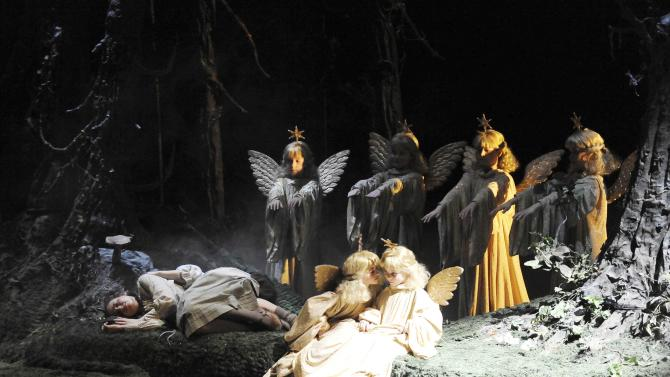 In this undated, publicly provided picture by Volksoper Vienna, Rebecca Nelsen, left on the ground, in the role of Gretel   performs with children dressed as angels  during a rehearsal of the opera Hansel and Gretel, by composer  Engelbert Humperdinck. at the Volksoper opera in Vienna.  (AP Photo/HONS/Dino Dimov,Volksoper Vienna)