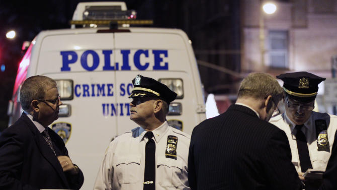 Police confer behind a crime scene unit vehicle in front of the luxury Manhattan apartment building where police say a nanny stabbed two small children to death in a bathtub and then stabbed herself in New York, Thursday, Oct. 25, 2012. Police say the children's mother found the scene after returning home with another child. (AP Photo/Kathy Willens)