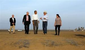 U.S. President Barack Obama walks with farmers Joe Del Bosque and Maria Del Bosque as he tours a drought affected farm field in Los Banos