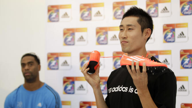 South Korean hurdler Park Tae-kyung, right,  posing for photographers with Adidas footwear flanked by injured U.S. sprinter Tyson Gay at the end of a news conference for the World Athletics Championships at the stadium in Daegu, South Korea, Thursday, Aug. 25, 2011.  (AP Photo/Matt Dunham)