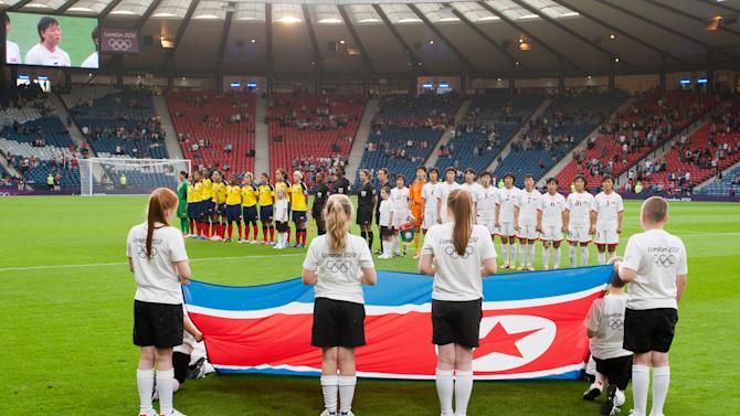CORRECTS GROUP MATCH TO G INSTEAD OF B- The North Korean women's soccer team sing their nation anthem before the group G match between Colombia and North Korea, prior to the start of the London 2012 Summer Olympics, Wednesday, July 25, 2012, at Hampden Park Stadium in Glasgow. (AP Photo/Chris Clark)