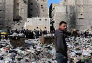 <p>Syrian people are pictured in a bazaar next to a garbage heap in the northern city of Aleppo, on February 14, 2013. Syria's army and rebels were preparing for a major battle for control of strategic airports in Aleppo, a watchdog said, four days after insurgents launched assaults on airbases in the northern province.</p>