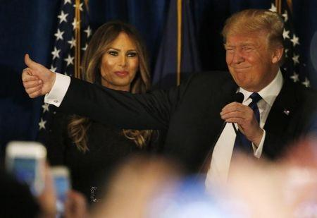 Republican U.S. presidential candidate Donald Trump reacts on stage as his wife Melania looks on at his 2016 New Hampshire presidential primary night rally in Manchester