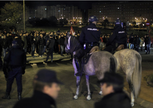 Protestors try to stop buses to run as the police stand guard outside a main bus garage during a general strike in Madrid, Spain, Wednesday, Nov. 14, 2012. Spain's main trade unions stage a general st
