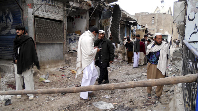 Local people look at damage caused by a blast in Hangu, Pakistan on Friday, Feb 1, 2013. A suicide bomber detonated his explosives outside a Shiite mosque in northwestern Pakistan as worshippers were leaving Friday prayers, killing several people and wounding scores in the latest apparent sectarian attack in the country, police said. (AP Photo/Abdul Basit)