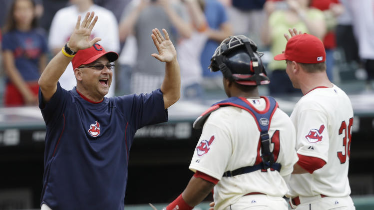 Cleveland Indians manager Terry Francona, left, gives high-fives to catcher Carlos Santana, center, and relief pitcher Joe Smith after they defeated the Seattle Mariners 6-0 in a baseball game on Sunday, May 19, 2013, in Cleveland. (AP Photo/Tony Dejak)