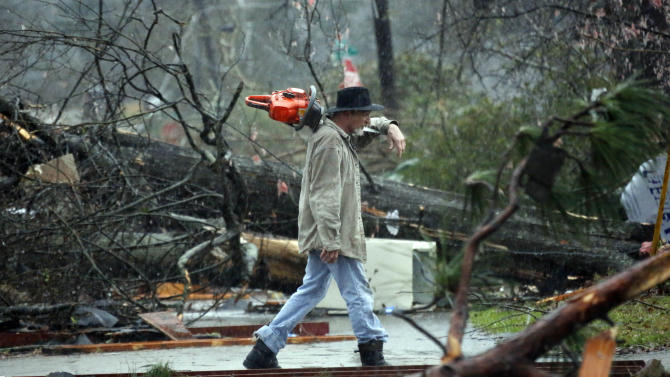 A Hattiesburg, Miss., resident walks through a tornado damaged neighborhood Monday, Feb. 11, 2013, after cutting away branches blocking a senior citizen's entrance to her home following a Sunday afternoon tornado that caused damage throughout the South Mississippi college town. (AP Photo/Rogelio V. Solis)