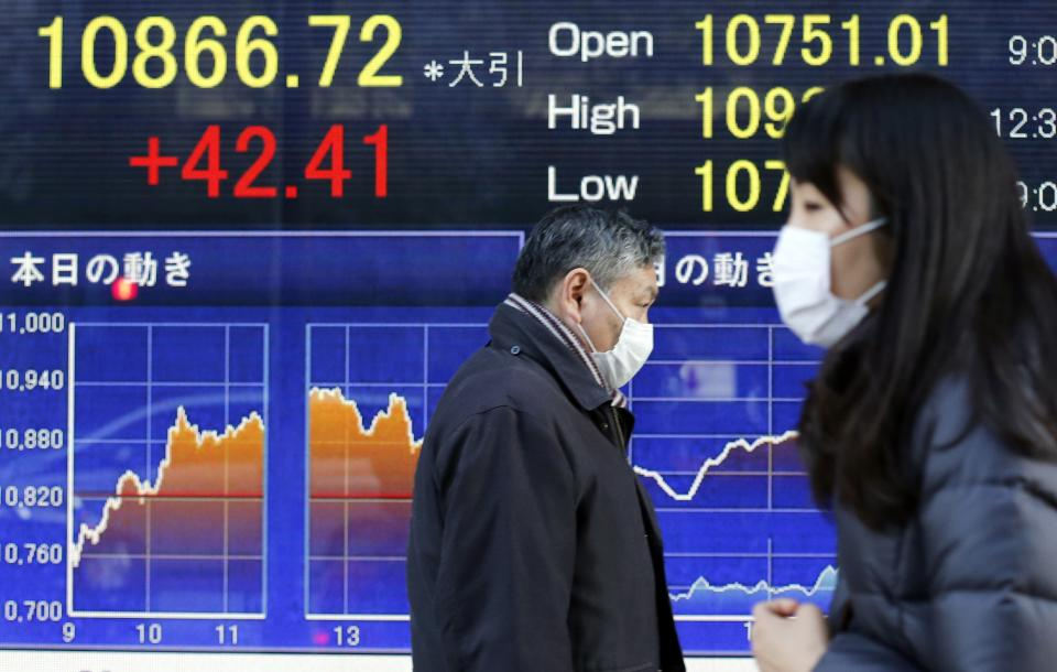 People walk by an electric stock index display of a securities firm in Tokyo Tuesday, Jan. 29, 2013. Asian stock markets posted modest gains Tuesday as the feel-good factor lingered from near-record highs on Wall Street and signs of an upswing in U.S. manufacturing.  (AP Photo/Koji Sasahara)
