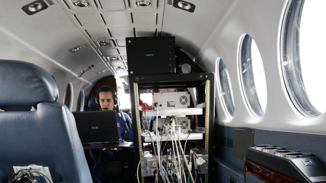 Lead Sensor Operator Andrew Halbach, left, operates the computers attached to the camera sensors in the floor of the plane during a National Oceanic and Atmospheric Administration flight to document coastal changes after Superstorm Sandy, Thursday, Nov. 1, 2012. (AP Photo/Alex Brandon)