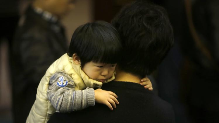 A child is cuddled as relatives of passengers aboard Malaysia Airlines flight MH370 attend a meeting with Malaysia Airlines at Lido Hotel in Beijing