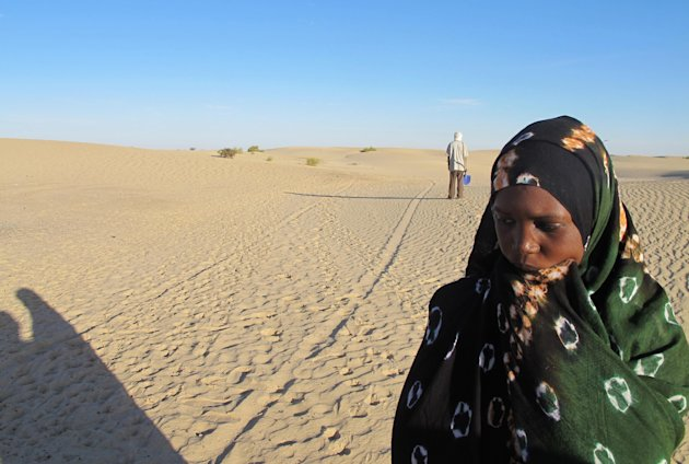 Ani Boka Arby stops in the desert in Timbuktu, Mali on Friday Feb. 8, 2013 a few hundred yards from the site where the body of her husband, Mohamed Lamine, was dumped. Ahead of her is her father who used a shovel to unearth his corpse. Lamine, an Arab, was last seen being led away at gunpoint by Malian soldiers on Jan. 28. Children found his body and that of another Arab man days later, lying facedown in the side of a dune on the outskirts of this desert capital. Human rights groups have warned that the military intervention to take back the territory in Mali's north which was occupied by al-Qaida-linked extremists last year, could open the door to reprisals killings. Especially vulnerable are ethnic minorities suspected of having supported the extremists, including the country's Arabs. (AP Photo/Rukmini Callimachi)