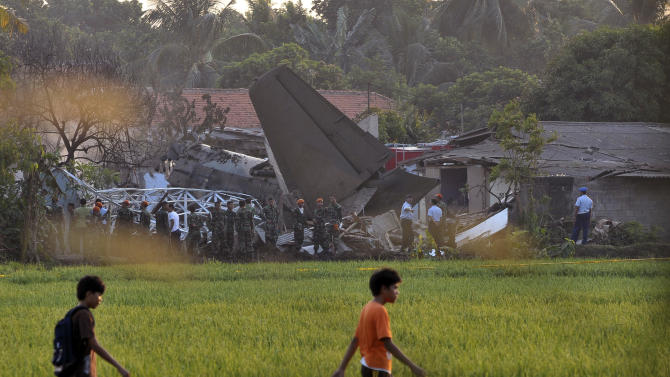 Youths walk through a rice field at the site of an Indonesian Air Force plane crash, seen in the background in Jakarta, Indonesia, Thursday, June 21, 2012. The Fokker F-27 turboprop plane slammed into homes and ignited a fireball in the crowded capital while trying to land Thursday, killing at least nine people, a military official said.   (AP Photo/Jefri Tarigan)
