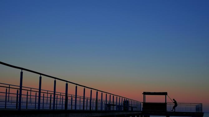 A man exercises at a dock on the beach during sunset the day before Christmas in the southern costal city of Larnaca, Cyprus, Wednesday, Dec. 24, 2014. (AP Photo/Petros Karadjias)