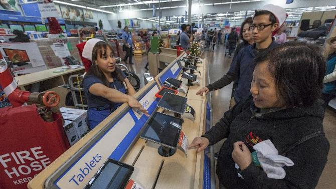 Walmart associate Danae Salcedo, left,  assists consumers shopping for tablets at the Pre-Black Friday event at the Walmart Supercenter store in Rosemead, Calif., Wednesday, Nov. 21, 2012. (AP Photo/Damian Dovarganes)