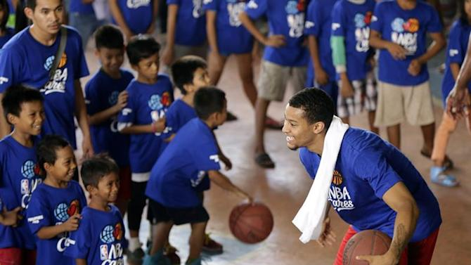 RIT08. Manila (Philippines), 22/05/2015.- Utah Jazz Trey Burke(R) reacts as they conduct a basketball clinic inside a covered court at a slum area in Manila, Philippines, 23 May 2015. NBA players from LA Lakers Jordan Clarkson, Utah Jazz Trey Burke and NBA Legend Horance Grant visited a slum area in Manila to conduct a basketball workshop for underprivileged youth. (Baloncesto, Jordania, Filipinas) EFE/EPA/RITCHIE B. TONGO