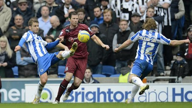 righton and Hove Albion's Andrea Orlandi (L) scores against Newcastle