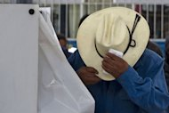 A man put on his hat after casting his vote at polling station in a school in San Lorenzo Tlacoyucan, in Mexico City. Voters in Mexico exhausted by drug violence looked set Sunday to return to power the Institutional Revolutionary Party (PRI) with its charismatic new leader Enrique Pena Nieto at the helm