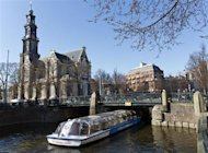 A tourist boat passes under a bridge next to the Westerkerk church in Amsterdam April 2, 2013. REUTERS/Michael Kooren