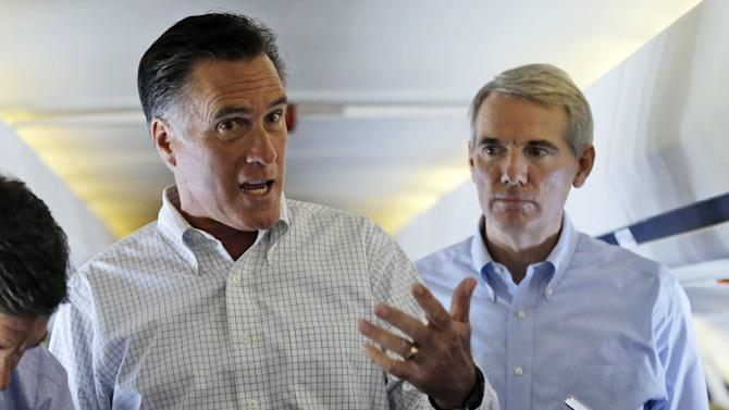Republican presidential candidate and former Massachusetts Gov. Mitt Romney speaks to reporters on his campaign plane en route to Denver, Sunday, Sept. 23, 2012, as Sen. Rob Portman, R-Ohio, listens at right. (AP Photo/Charles Dharapak)