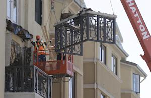 Workers remove part of a balcony that collapsed at…