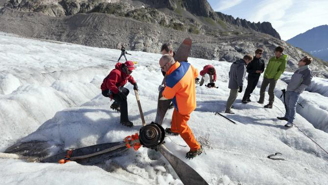 """Mountain rescuers recover the propeller of US warplane C-53 Skytrooper """"Dakota"""" that crashed in 1946, on the Gauli glacier in the Bernese Alps, Switzerland, Thursday Aug. 9, 2012. Three young climbers discovered a propeller piece of the legendary airplane at the end of July 2012. The Dakota crash on the Gauli Glacier on Nov. 19, 1946 was a turning point in alpine rescue and an international media event. The aircraft, coming from Austria bound for Italy, collided with the Gauli glacier in poor visibility. On board were four crew members and eight passengers. Among the eight passengers were high-ranking officers of the U.S. armed forces with some of their relatives. Several people were injured, but there were no fatalities. The propeller will be transported to the near Gauli cabin. (AP Photo/Keystone, Gaetan Bally)"""