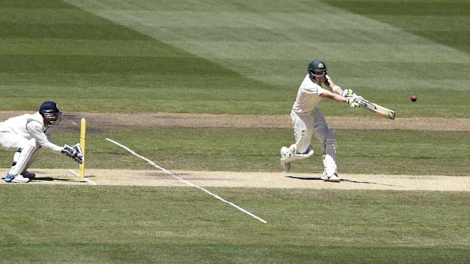 Australia's Steve Smith, right, moves down the wicket to drive the ball in front of India's wicketkeeper MS Dhoni on the second day of their cricket test match in Melbourne, Australia, Saturday, Dec. 27, 2014. Australia are all out for 530 in their first innings. (AP Photo/Andy Brownbill)