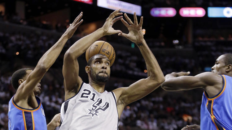 San Antonio Spurs' Tim Duncan (21) loses control of the ball as Oklahoma Thunder's Thabo Sefolosha, left,  of Switzerland, and Serge Ibaka, right, defend during the first quarter of an NBA basketball game, Thursday, Nov. 1, 2012, in San Antonio. (AP Photo/Eric Gay)