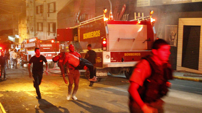 A man carries an injured man, victim of a fire at the Kiss  club in Santa Maria city,  Rio Grande do Sul state, Brazil, early Sunday, Jan. 27, 2013.  Firefighters say that the death toll from a fire that swept through a crowded nightclub in southern Brazil has risen to 180. Officials say the fire broke out  while a band was performing. At least 200 people have been injured. (AP Photo/Agencia RBS)