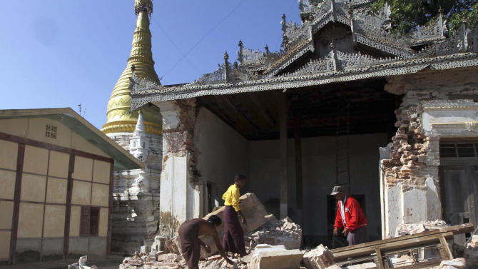Three men try to clear debris after a pagoda was damaged by Sunday's strong earthquake in Kyaukmyaung township in Shwebo, Sagaing Division, northwest of Mandalay, Myanmar, Monday, Nov. 12, 2012. The earthquake collapsed a bridge and damaged ancient Buddhist pagodas in northern Myanmar, and piecemeal reports from the underdeveloped mining region said mines collapsed and as many as 12 people were feared dead. (AP Photo/Khin Maung Win)