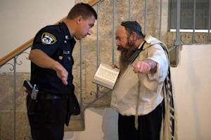 An Israeli police man askes a Jewish man reciting the …