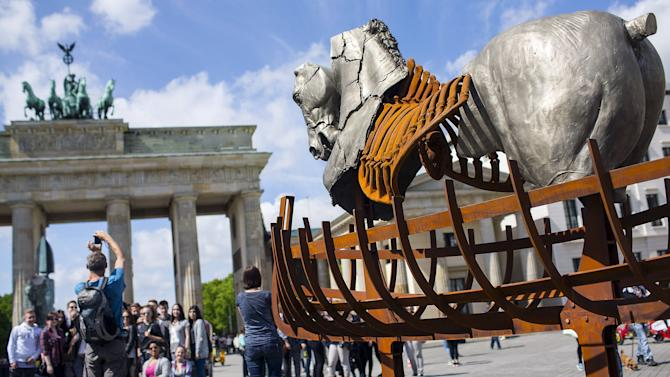 "Man takes a picture near a piece of a travelling art exhibition called ""Lapidarium"" by Mexican artist Gustavo Aceves, in front of Brandenburg Gate in Berlin, Germany"