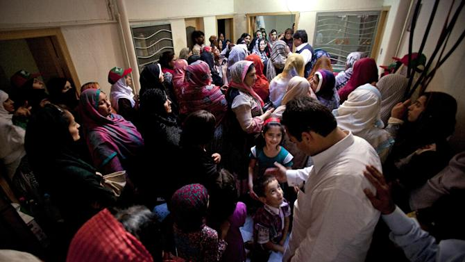 In this Friday, May 3, 2013 photo, an election candidate interacts with women during a door-to-door election campaign held indoors due to a security threat, in Rawalpindi, Pakistan. As the country gets set to vote in the upcoming nationwide election that will see a transfer of power from one civilian government to the next -- a first for Pakistan -- women still face an uphill battle to make their voices heard in the political process. (AP Photo/B.K. Bangash)