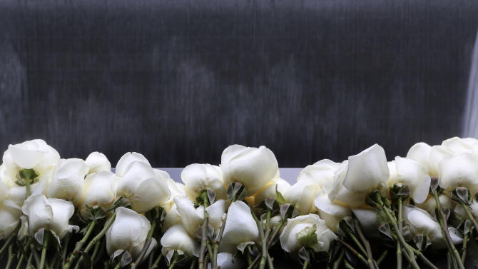 White roses are placed on the names of the six people who were killed 20 years ago in the first terrorist attack on the World Trade Center in New York, before the start of a ceremony to remember them Tuesday, Feb. 26, 2013. About 50 people attended the ceremony, held at the 9/11 memorial, where the twin towers were destroyed eight years later. (AP Photo/Mary Altaffer)