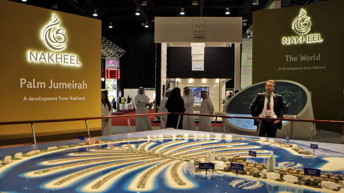 FILE - In this file photo taken Monday Oct. 5, 2009, a visitor looks at the Palm Jumeirah model at the Nakheel stand at the Cityscape exhibition in Dubai, United Arab Emirates. Dubai's developer Nakheel behind the famed man-made palm-shaped islands said Wednesday, Aug. 20, 2014, that it is repaying 7.9 billion dirhams, or roughly $2.15 billion this month - nearly four years before the last installment is due. (AP Photo/Kamran Jebreili, File)