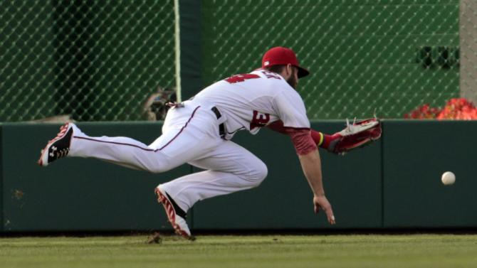 Washington Nationals left fielder Bryce Harper dives for but misses a ball hit by San Diego Padres' Chris Denorfia during a baseball game at Nationals Park, Friday, July 5, 2013, in Washington. (AP Photo/Alex Brandon)