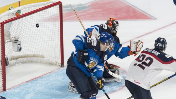 The puck sails into the net past Finland goaltender Juuse Saros on a goal by Slovakia's Matus Holenda during the second period of a round-robin game at the hockey World Junior Championship, Saturday, Dec. 27, 2014, in Montreal. (AP Photo/The Canadian Press, Graham Hughes)