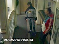 A man dressed as Batman and a burglary suspect stand in a police station in Bradford, northern England, on February 25, 2013, in this still photograph taken from video and provided by West Yorkshire Police on March 4, 2013. A mystery man dressed as Batman demonstrated the same crime-fighting skills as the caped crusader when he handed over a suspect wanted for burglary in Britain. Closed-circuit television footage showed a portly figure wearing an ill-fitting costume including gloves, cape and mask, bringing a 27-year-old man to a police station in Bradford in northern England.  REUTERS/West Yorkshire Police/Handout   (BRITAIN - Tags: CRIME LAW SOCIETY)   